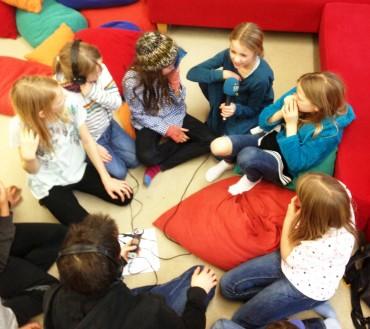 In der Bücherei der Schule werden die Dialoge für das Weihnachtshörspiel aufgenommen